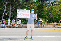 """A man holds a sign reading """"The Trumps are an embarrassment to our country"""" as a small group of Biden supporters gather by the roadside to protest before Donald Trump, Jr., son of president Donald Trump and a rising Republican political star, speaks at an outdoor campaign rally at The Lobster Trap in North Conway, New Hampshire, on Thu., Sept. 24, 2020."""