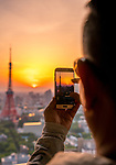 Person taking photo on mobile phone of the sunset from the observation deck of the World Trade Center Building located in Hamamatsuchō, Minato, Tokyo.
