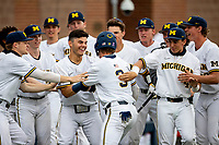 Michigan Wolverines first baseman Jimmy Obertop (8) celebrates with teammates after Ted Burton (3) scores against the Ohio State Buckeyes on April 9, 2021 in NCAA baseball action at Ray Fisher Stadium in Ann Arbor, Michigan. Ohio State beat the Wolverines 7-4. (Andrew Woolley/Four Seam Images)