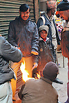 A group warms themselves around a fire at Chowk Bazaar, Darjeeling