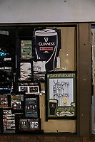 """A sign reading """"Welcome Back Friends"""" is seen in the window of the closed storefront next to The Burren restaurant and bar in Davis Square in Somerville, Massachusetts, on Tue., Jan. 26, 2021."""