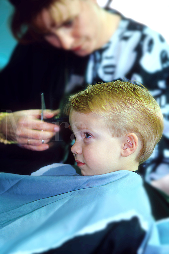 Child age 4 accepting haircut with less than modest enthusiasm.  Number 1 of a series of 3 images