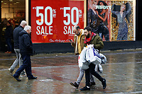 Last minute Christmas shoppers walk past huge 50% sale signs in Oxford Street, in the city centre of Swansea, Wales, UK. Sunday 24 December 2017