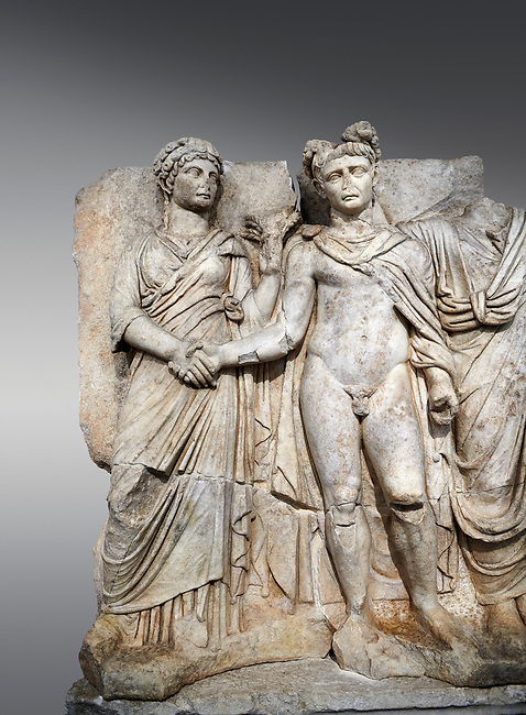 """Roman Sebasteion relief sculpture of emperor Claudius and Agrippina, Aphrodisias Museum, Aphrodisias, Turkey. <br /> <br /> Claudius in heroic nudity and military cloak shakes hands with his wife Agrippina and is crowned by the Roman people or the Senate wearing a toga. The subject is imperial concord with the traditional Roman state. Agrippina holds ears of wheat: like Demeter goddess of fertility. The emperor is crowned with an oak wreath, the Corona civica or """"citizen crow"""", awarded to Roman leaders for saving citizens lives: the emperor id therefore represented as saviour of the people."""