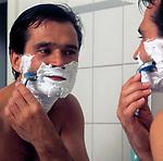 Mann mit nacktem Oberkoerper vorm Spiegel bei Nassrasur | man, wet shaving, looking into mirror