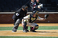 Wake Forest Demon Deacons catcher Ben Breazeale (9) sets a target as home plate umpire Donald Gilmore looks over his shoulder during the game against the Virginia Tech Hokies at Wake Forest Baseball Park on March 7, 2015 in Winston-Salem, North Carolina.  The Hokies defeated the Demon Deacons 12-7 in game one of a double-header.   (Brian Westerholt/Four Seam Images)
