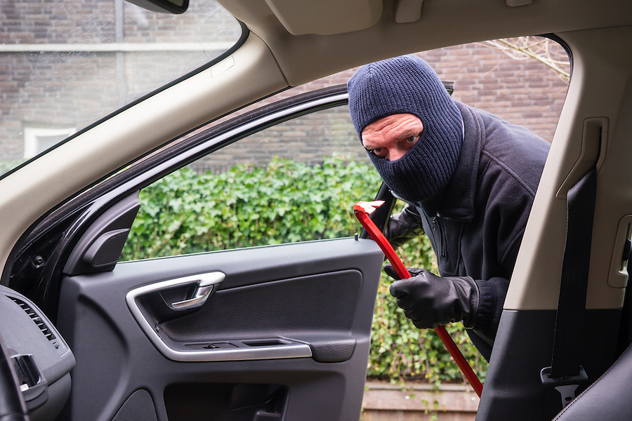 A burglar in action to rob something out of a car