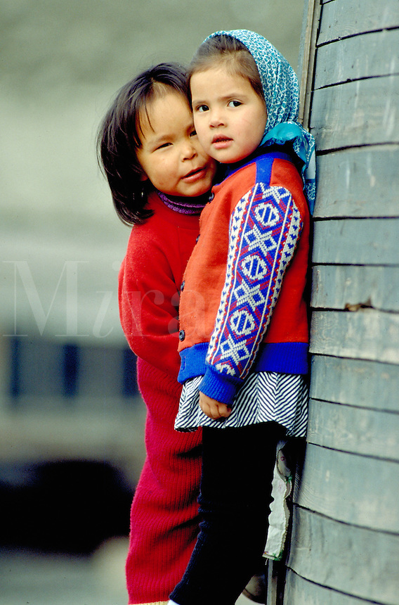 A six year old Inuit girl whispers into the ear of her friend whose facial features are clearly Russian, diversity, multiethnic, children, friendship. Little girls of two different ethnic origins - Inuit and Russian. Uelen North slope of Siberia Russia Vi