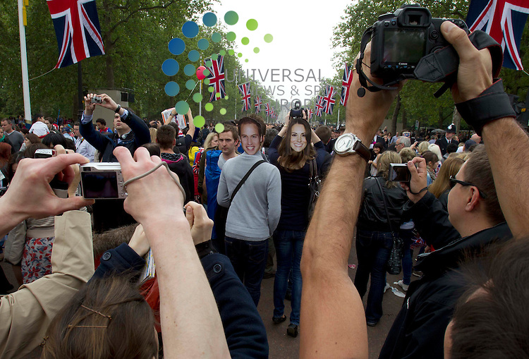 A couple of tourist walk down the Mall with Royal face masks on after Princess Kate and Prince William drive to the Buckingham Palace. .Picture: Maurice McDonald/Universal News And Sport (Europe).29 April 2011..
