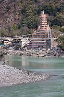 India, Rishikesh.  Tera Manzil Hindu Temple, holding numerous shrines to various Hindu gods.   Ganges (Ganga) River in foreground.