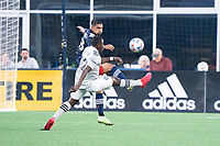 FOXBOROUGH, MA - JULY 25: A.J. DeLaGarza #28 of New England Revolution and Sunusi Ibrahim #22 of CF Montreal battle for the ball during a game between CF Montreal and New England Revolution at Gillette Stadium on July 25, 2021 in Foxborough, Massachusetts.