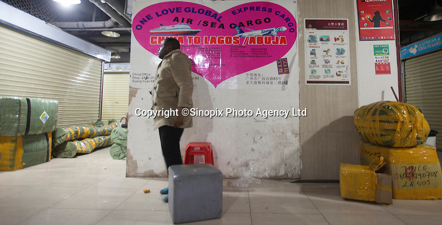 An African trader seen by boxes destined for Africa in an area of Guangzhou known to locals as 'Chocolate City', Guangzhou, Guangdong Province, China, 08 December 2014. The health authorities of Guangzhou are said to be stepping up their monitoring of the African community in light of the ongoing outbreak of the Ebola virus disease in West Africa.