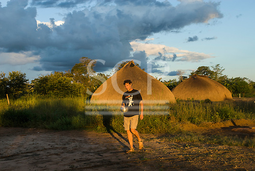 Xingu Indigenous Park, Mato Grosso State, Brazil. Aldeia Aweti. Patrick Cunningham in the village at sunset.