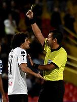 BOGOTÁ - COLOMBIA, 15-08-2018: Julio Bascuñán (Der.) árbitro Chileno, muestra tarjeta amarilla a Blas Cáceres (Izq.) jugador de General Díaz (PAR), durante partido de vuelta entre Millonarios (COL) y General Díaz (PAR), de la segunda fase por la Copa Conmebol Sudamericana 2018, en el estadio Nemesio Camacho El Campin, de la ciudad de Bogotá. / Julio Bascuñán, Chilean referee, shows yellow card to Blas Caceres (L) player of General Diaz (PAR), during a match of the second leg between Millonarios (COL) and General Diaz (PAR), of the second phase for the Conmebol Sudamericana Cup 2018 in the Nemesio Camacho El Campin stadium in Bogota city. VizzorImage / Luis Ramirez / Staff.