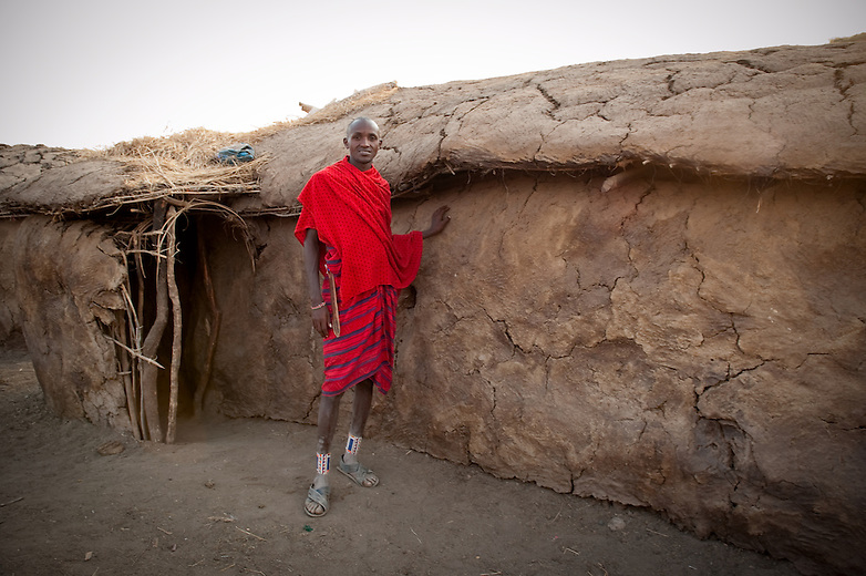 """Masai dwellings are oval in shape, low roofed and have a skeleton structure made from branches pasted with fresh cow dung which bakes hard under the hot sun.  The structural framework is formed of timber poles fixed directly into the ground and interwoven with branches that are plastered with a mix of mud, sticks, grass, cow dung and human urine, and ash. Women do the entire job of building the huts and are also responsible for maintenance especially during wet weather when there may be leakage. One hut may take up to three weeks to complete.  Masai huts are very small with perhaps two """"rooms"""" and not enough room for these tall Maasai to stand upright or lie fully stretched. They are also very dark with a small door-way and tiny hole in the roof that lets a little light in and releases smoke from the fires."""