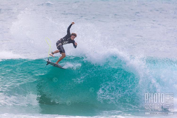 A young local surfer performs an aerial maneuver, Sequence #1, Po'ipu Beach Park, Kaua'i.