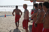 May 23, 2013: Ocean Beach, San Diego, California, USA:  At the San Diego Lifeguard Bronze Memorial Dedication Ceremony, 13 Lifeguards representing the 13 victims of the 1918 drownings made their way to the water and formed a ceremonial circle..