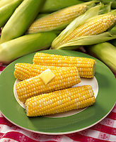 Corn on the cob plated with melting butter.