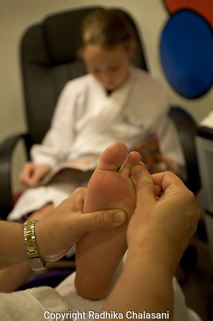 """SAN ANTONIO, TEXAS-MARCH 25: Bailey Palmer (10) gets a foot massage during a pedicure at Spaaht, the two year-old spa that caters solely to those under 17,  at the Hyatt Regency Hill Country Resort March 25, 2005 in San Antonio. Bailey had her first manicure when she was 4 years-old and she and her friends often have spa parties back home in Pennsylvania. She says, """"I am a bright color person"""" and likes purple, pink and lime green polish. (Photo by Radhika Chalasani)"""
