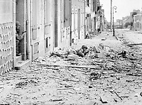 Americans take shelter during mop-up of Brest.  Crouching behind a pile of rubble, a U.S. soldier watches for German snipers in the streets of Brest, while a companion covers him from behind a doorway.  September 1944.  INP.  (OWI)<br /> Exact Date Shot Unknown<br /> NARA FILE #:  208-AA-19Z-1<br /> WAR & CONFLICT BOOK #:  1054