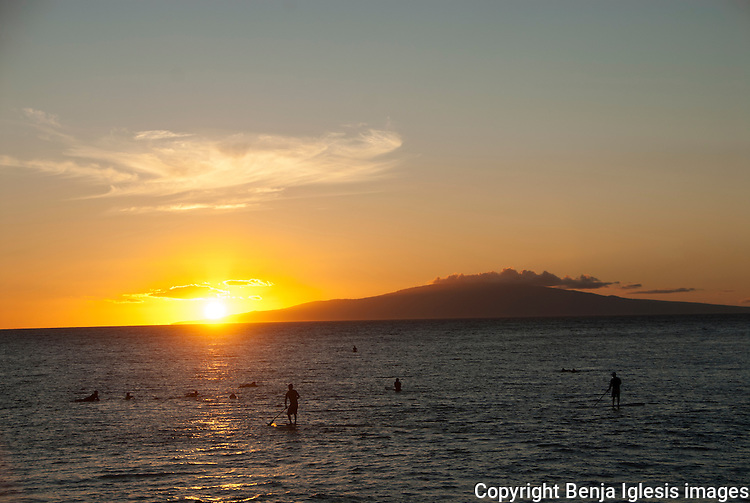 A few standup paddlers and surfers enjoying the sunset at the covepark with the island of Lanai as a background.
