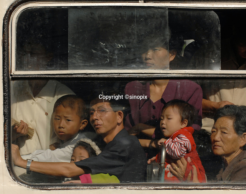 A packed trolley bus on the street of PyongYang, North Korea.