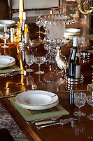 Detail of a place setting on the table in the formal dining room. Silverware grouse scratch around amongst the glassware
