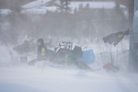 Jeff King makes camp in Kaltag for his dogs as high winds blow around him 2006 Iditarod Western AK Winter