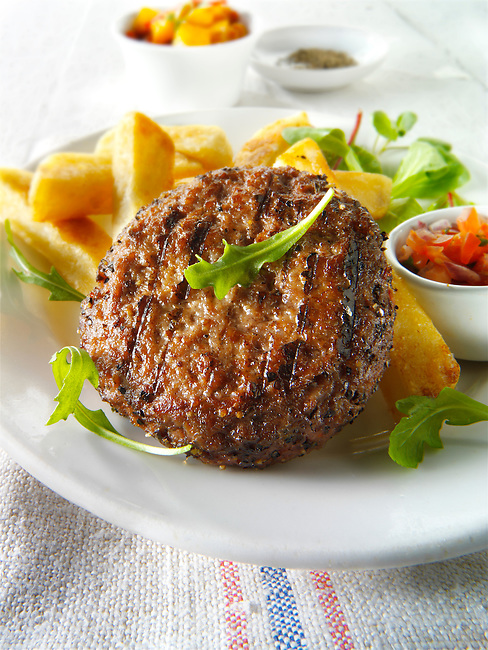 Char grilled beef burger  with chunky chips and salad photo. Funky Stock Photos