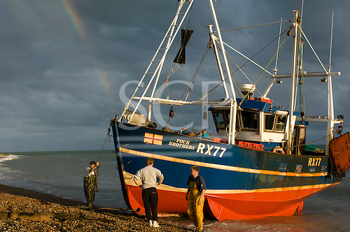 Hastings, East Sussex, England. Hastings, East Sussex, England.  Fishing boat Four Brothers on shoreline with rainbow and three fishermen in the afternoon sun.