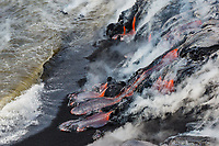 Koi-Shaped Lava: Lava flows out onto a black sand beach on the Big Island, creating koi (fish) shapes; shore break approaches the lava, cooling it and creating steam.