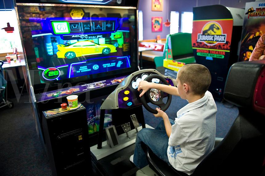 Boy playing an arcade video game.