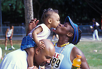 Mother runner kisses her daughter on father's shoulders at the Honolulu Marathon
