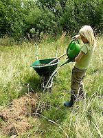Kind, Junge pflanzt einen Obstbaum, Kirschbaum auf einer Wiese, Streuobstwiese, füllt Wasser in das Pflanzloch
