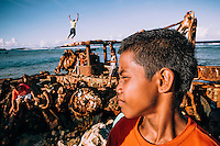 Hiroshi, 13, plays along with his friends on the rusty remains of machines abandoned on the coast of the island.