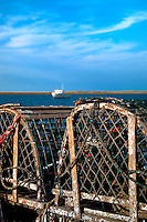 Wooden lobster traps and boat in Nauset Harbor, Orleans, Cape Cod, MA, USA