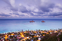 A sunset view from the top of Pillbox Hike in Kailua of the Mokulua Islands near Lanikai, Windward O'ahu; Lanikai's street lights glow amongst its residences.