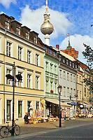 Berlin, Germany.   Street with souvenir shops and restaurants in Nikolai-viertel.  Fernsehturm in distance.