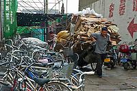 Man pulling a large cart full of carton, Datong, Shanxi, China.