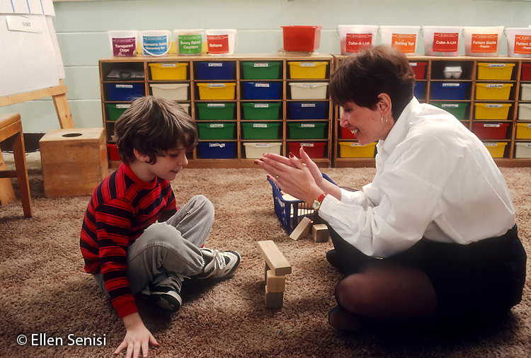 MR / Schenectady, New York. Yates Arts-in-Education Magnet School. Urban public school. Self-contained special education classroom. Special education teacher shows positive reinforcement by clapping for multiply-handicapped student who has just built a simple structure with wooden blocks. Boy (age 8) has been diagnosed with autism, epilepsy, ADHD, hearing impairment, and expressive and receptive language delays (no verbal output at this time). MR: Cou3, Mon4. ID: BO-JK. © Ellen B. Senisi