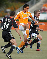 Houston Dynamo forward Brian Ching (25) settles the ball as D.C. United midfielders Ben Olsen (14) and Brian Carroll (16) mark Ching.  Houston Dynamo defeated D.C. United 1-0 at Robertson Stadium in Houston, TX on July 8, 2007.