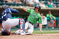 Gwinnett Stripers catcher Rob Brantly (8) slides into home plate as catcher Eric Haase (13) looks to apply the tag during a game against the Columbus Clippers on May 17, 2018 at Huntington Park in Columbus, Ohio.  Gwinnett defeated Columbus 6-0.  (Mike Janes/Four Seam Images)
