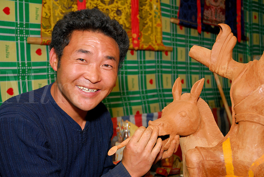 Tibetan sculptor creating a hollow clay horse and rider in an alley workshop, Barkhor, Lhasa, Tibet.