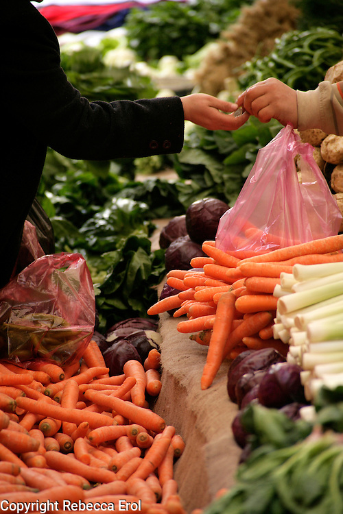 Money exchanging hands at a fresh fruit and vegetable market