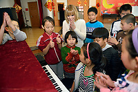 "Swiss singer and TV presenter Francine Jordi listens a student playing piano while visiting ""SOS Kinderdorf"" in Tianjin, China. 22-Mar-2016"