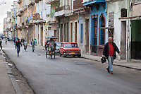 Cuba, Havana.  Early Morning Central Havana Street Scene.  Pedestrians, Bicycle Taxi.