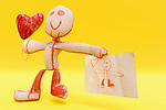 Digital render of a proud and loving child-like character holding a drawing in one hand and a hearth shaped balloon in the other as a big smile appears on its hand-drawn face. The 3D character is inspired by a real world drawing a five-year-old child made for his mother.