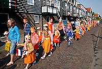 Tijdens Koningsdag lopen veel  inwoners van Marken  in klederdracht met oranje accenten
