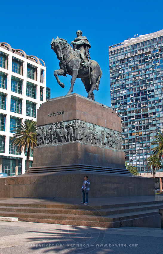 Plaza Independencia Independence Square with the mausoleum of General Jose Artigas with equestrian statue on the square. The general on a horse.. A woman standing by the imposing stone monument. Modern office buildings in the background. Montevideo, Uruguay, South America