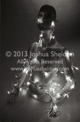 Christmas lights draped over mannequin torso<br />